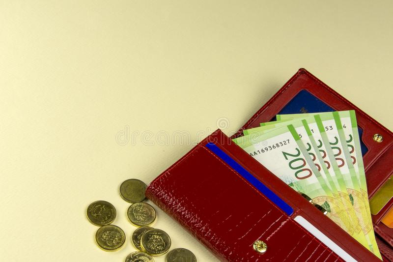 Red woman wallet. Banknotes in two hundred Russian rubles. A few coins. Beige background. Russia royalty free stock photography