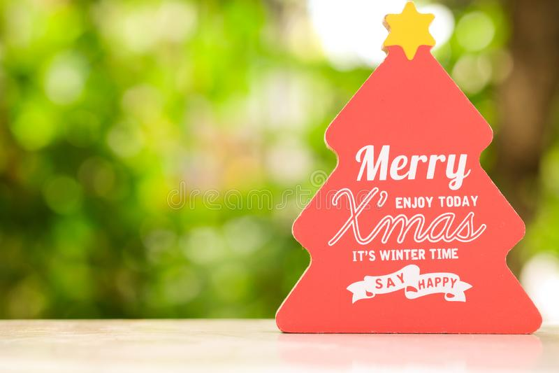 Red wood block with merry christmas word in front of green tree use as holiday and celebrate new year stock photography