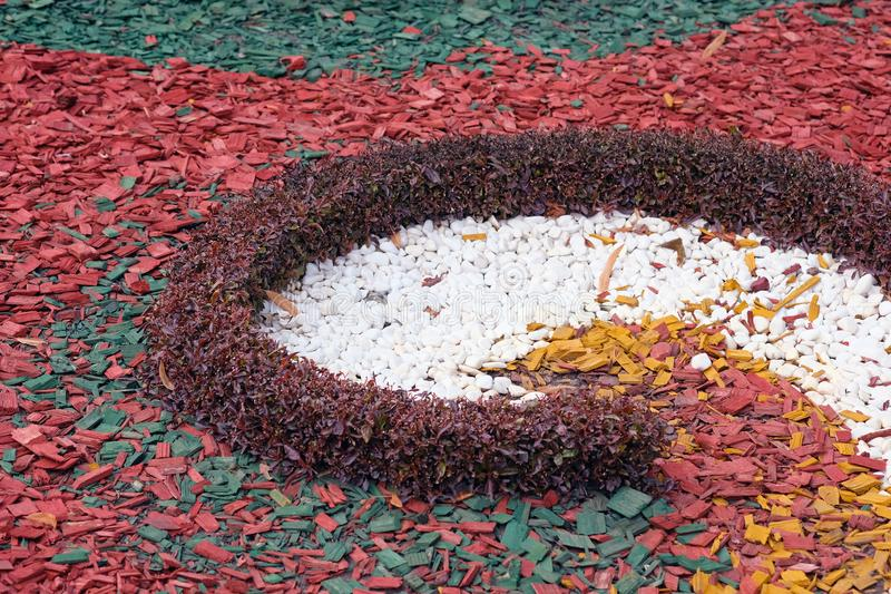 Red wood chips. White stones for decoration of flower beds. royalty free stock images