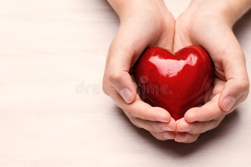 Red wood heart in child hands royalty free stock image