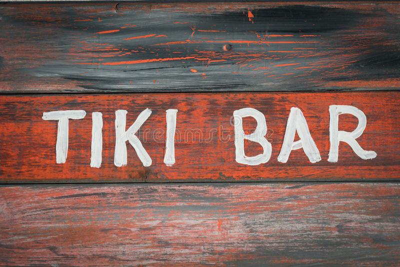Red wood tiki bar sign. A red wood sign with the words tiki bar painted in white letters stock images