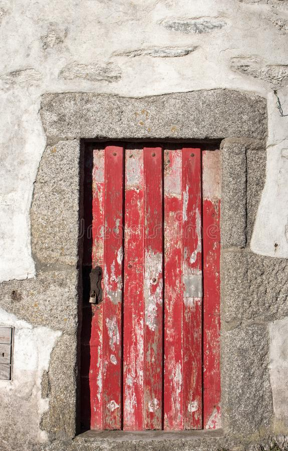 Red wooden aged door in stone wall. Ancient abandoned building. Medieval rustic architecture. stock photography
