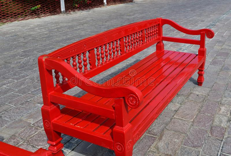 Red wooden bench outdoors in Doha, Qatar. The Red wooden bench outdoors in Doha, Qatar stock photo