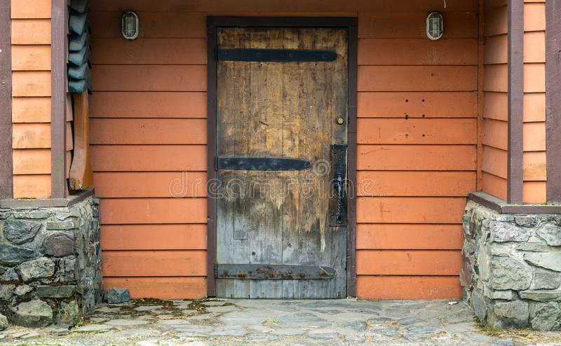 Red wooden building wall with an old weathered wooden door stock image