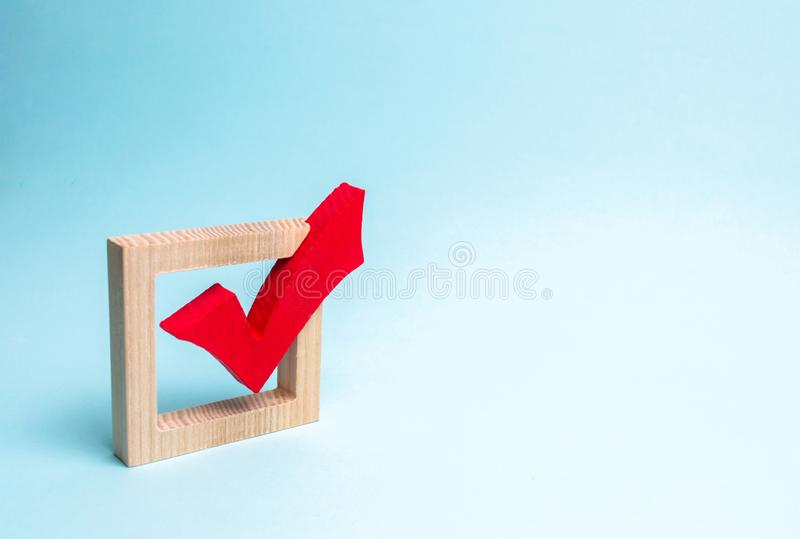 Red wooden checkmark for voting on elections on a blue background. Presidency or parliamentary elections, a referendum. Survey. Of the population, statistics stock image