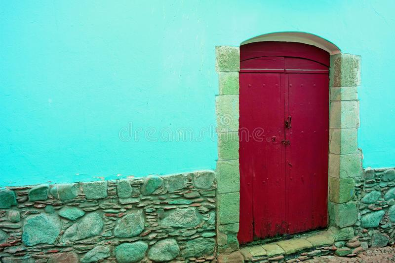 Red wooden door on the concrete and stone wall in aqua blue color royalty free stock image