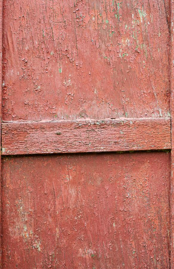 Red wooden door fragment with peeled paint and horizontal plank in the middle, vertical shot stock photo