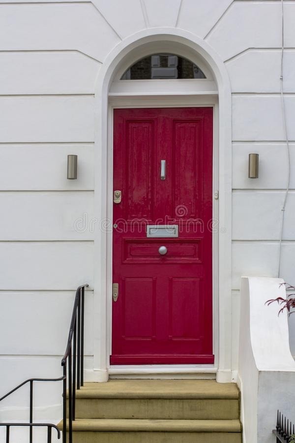 Red Wooden Entrance Door to residential building in London. Typical door in the English style. stock photos