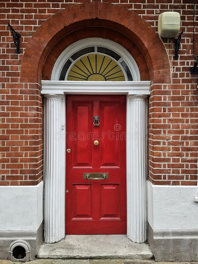 Red wooden front door with arch and pillars at a brick building. Red wooden front door with arch and pillars at a brick building's frontage royalty free stock photos