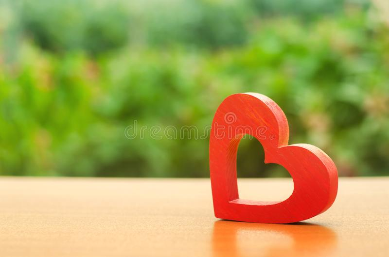 A red wooden heart on nature background. The secret of relationships and the rules of a strong family. Strong love affair. Secrets stock photography