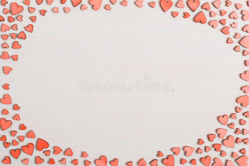 Red wooden hearts on a white table with place for text. Background for greeting card or congratulations on Valentine`s Day. Copy stock images