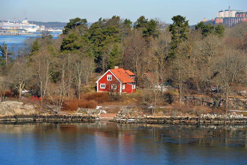 Red wooden house on background of Stockholm port. Sweden royalty free stock photo