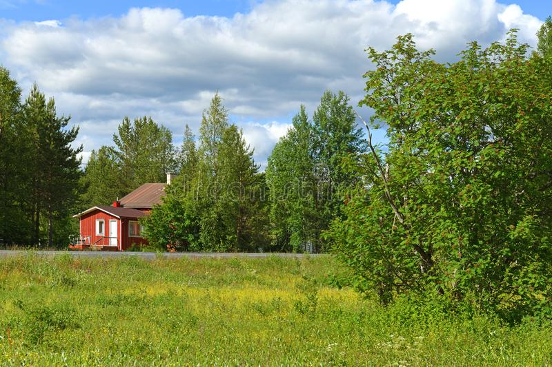 Red wooden house in forest near road. Finnish Lapland royalty free stock images