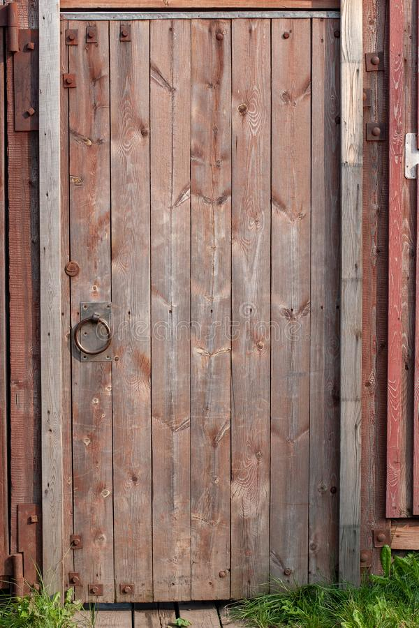 Red wooden old door in the fence with iron hinges and a round handle. The paint is faded. A lot of knots, bolts, nails. Vertical frame royalty free stock image