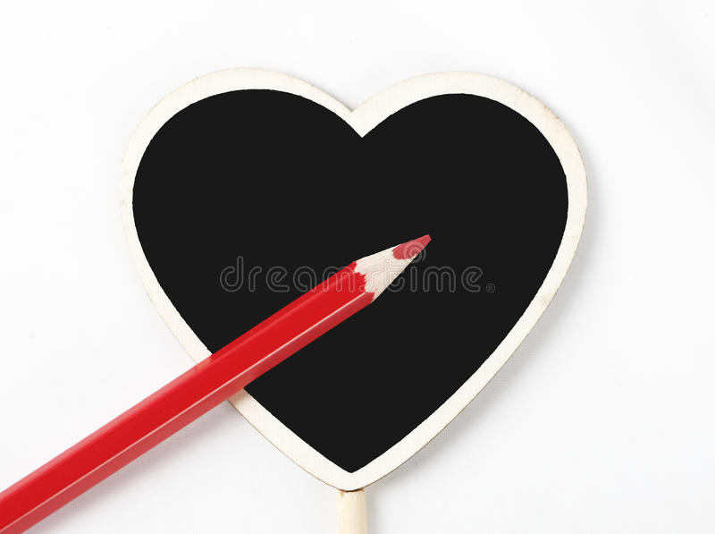 Red wooden pencil on a blackboard with heart shape on white background. Isolated royalty free stock photo