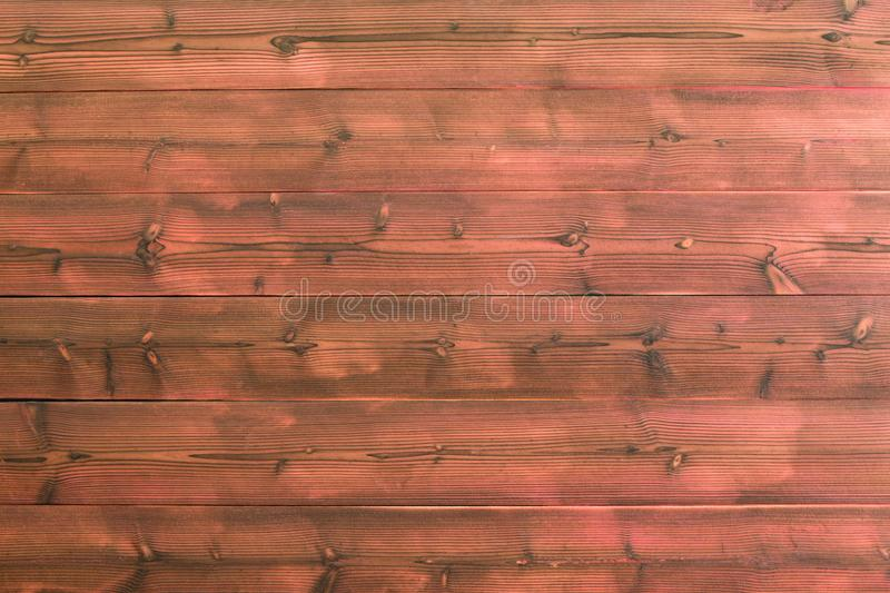 Red wooden plank wall with visible knots in wood. Red wooden plank wall background with visible knots in wood and black marks along grain. Includes copy space royalty free stock photography