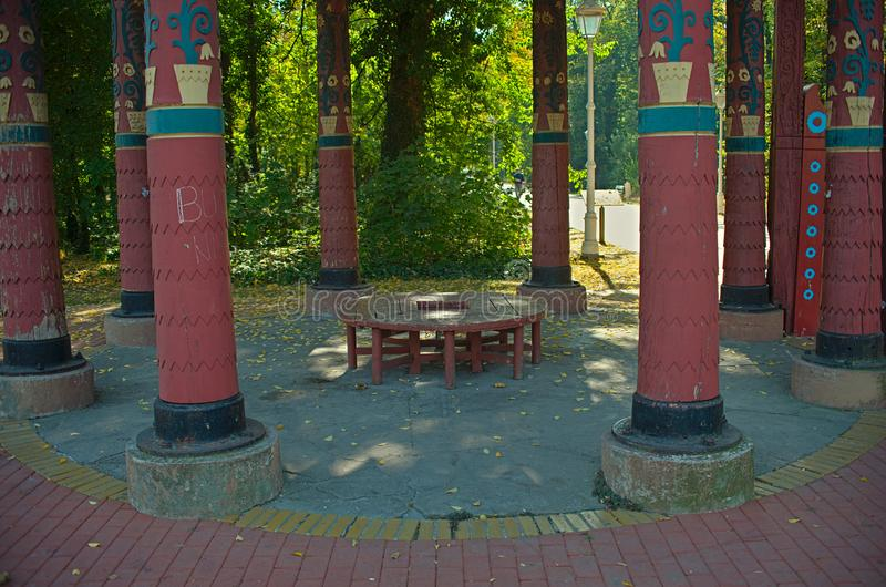 Red wooden round bench in a park surrounded by big red pillars.  stock photography