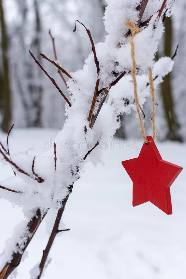 Red wooden star on snowy Christmas tree in winter forest. Christmas and Happy New Year concept. Winter holidays symbol. Frosty forest in snow. Christmas royalty free stock photography