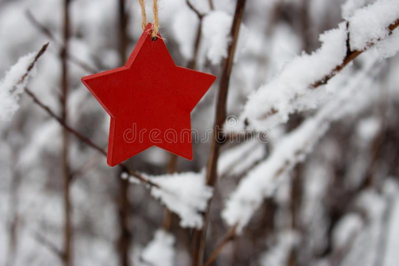 Red wooden star on snowy Christmas tree in winter forest. Christmas and Happy New Year concept. Winter holidays symbol. Frosty forest in snow. Christmas royalty free stock image