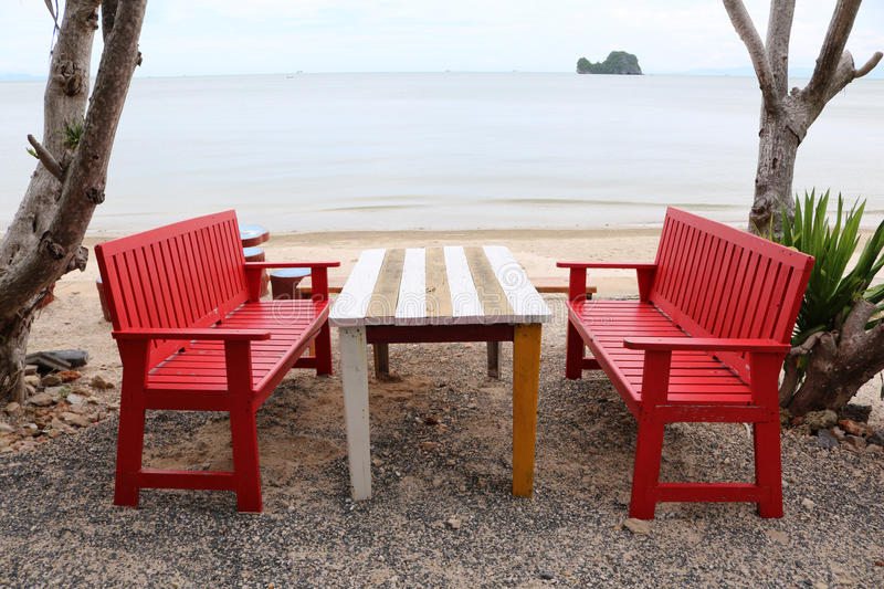 Red wooden table and chairs on the beach. stock images