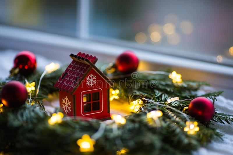 Red wooden toy house surrounded with fir-tree wreath decorated with warm garland lights and little Christmas balls near window. stock photo