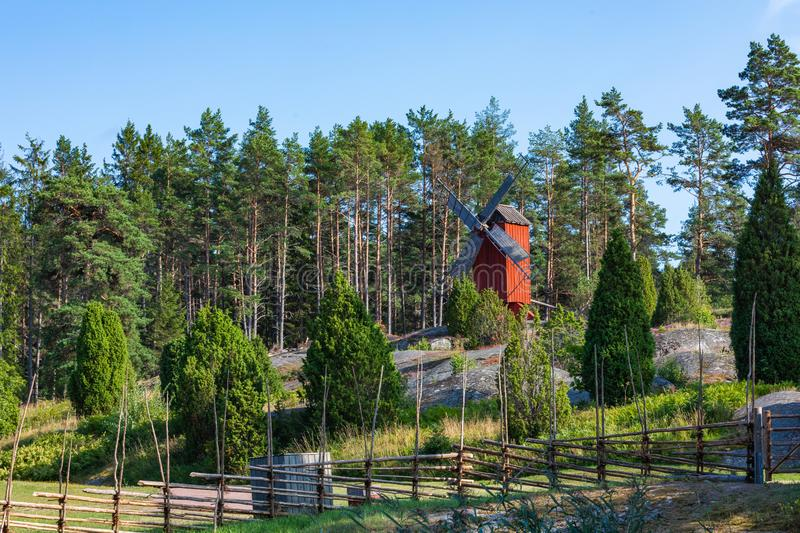 Red wooden windmill in a old vintage rural landscape at Aland islands, Finland. Jan Karlsgarden open air museum. Ethnographic park stock photography