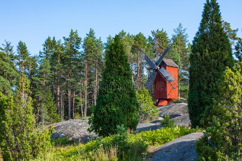 Red wooden windmill in a old vintage rural landscape at Aland islands, Finland. Jan Karlsgarden open air museum. Ethnographic park royalty free stock image