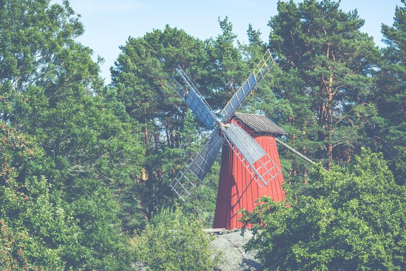 Red wooden windmill in a old vintage rural landscape at Aland islands, Finland. Jan Karlsgarden open air museum. Ethnographic park royalty free stock photography