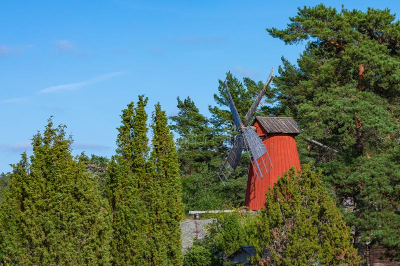 Red wooden windmill in a old vintage rural landscape at Aland islands, Finland. Jan Karlsgarden open air museum. Ethnographic park.  royalty free stock images