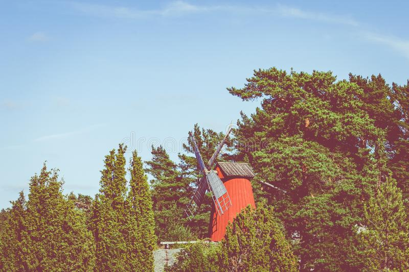 Red wooden windmill in a old vintage rural landscape at Aland islands, Finland. Jan Karlsgarden open air museum. Ethnographic park.  stock image