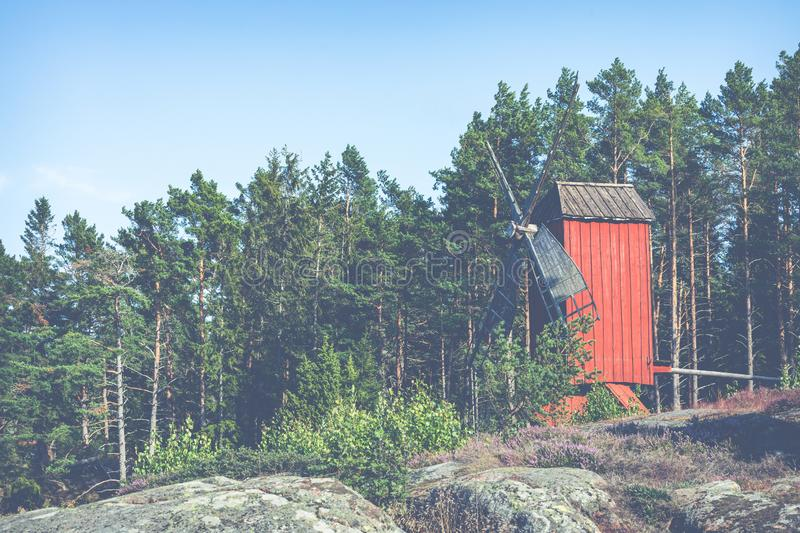 Red wooden windmill in a old vintage rural landscape at Aland islands, Finland. Jan Karlsgarden open air museum. Ethnographic park.  stock photography