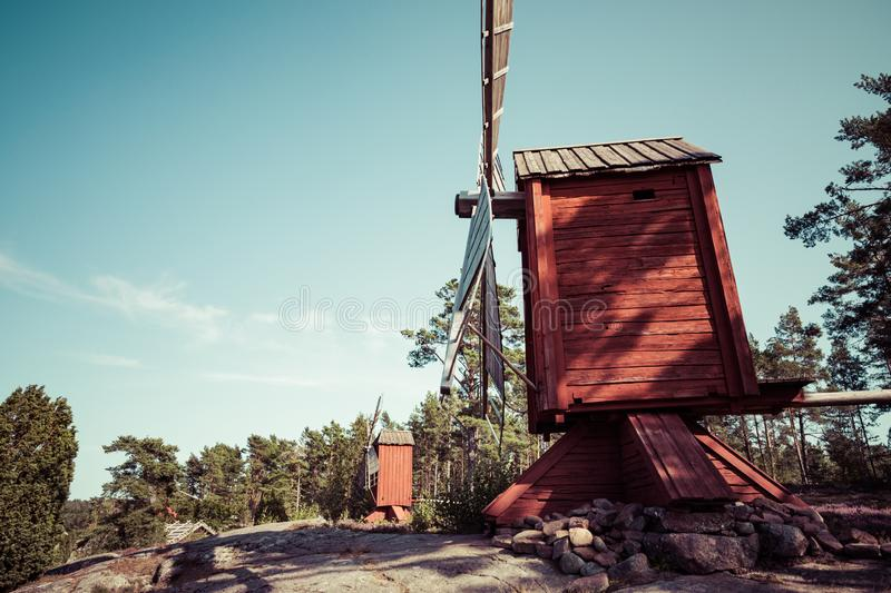 Red wooden windmill in a old vintage rural landscape at Aland islands, Finland. Jan Karlsgarden open air museum. Ethnographic park stock photos
