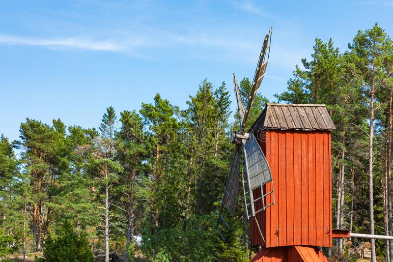 Red wooden windmill in a old vintage rural landscape at Aland islands, Finland. Jan Karlsgarden open air museum. Ethnographic park royalty free stock photos