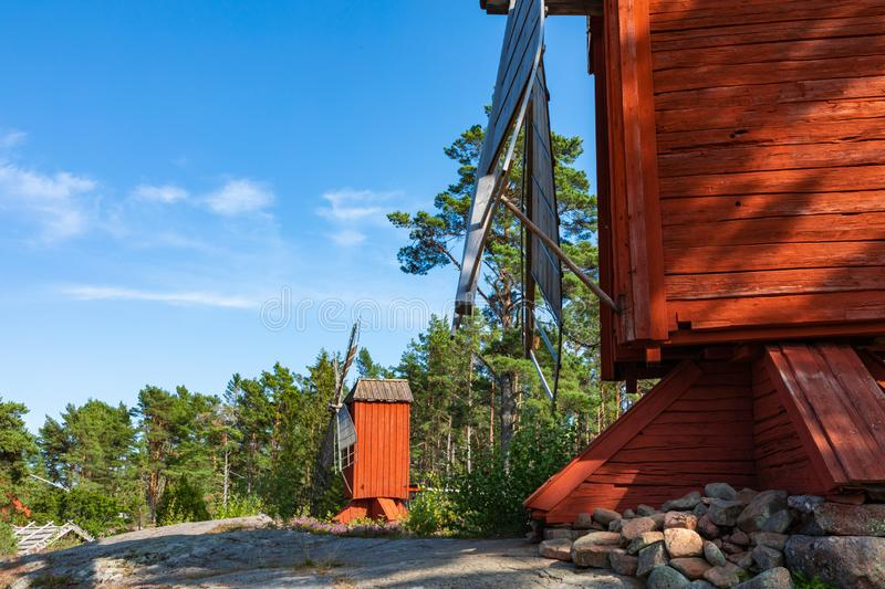 Red wooden windmill in a old vintage rural landscape at Aland islands, Finland. Jan Karlsgarden open air museum. Ethnographic park royalty free stock images