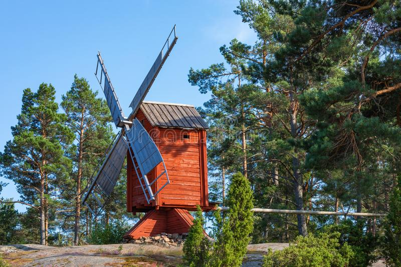 Red wooden windmill in a old vintage rural landscape at Aland islands, Finland. Jan Karlsgarden open air museum. Ethnographic park stock photo
