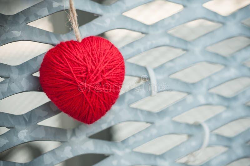 red woolen heart in outdoor on metallic grid royalty free stock photo