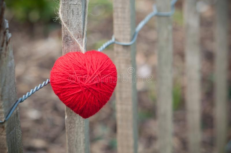 red woolen heart in outdoor on wooden fence royalty free stock photography