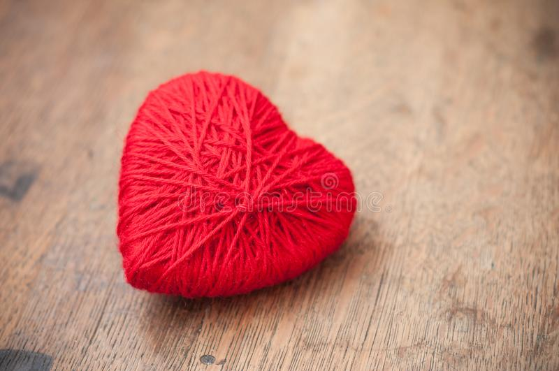 red woolen heart on wooden table background stock photography