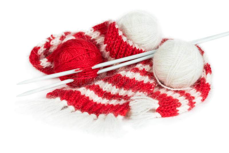 Red woolen scarf, knitting needles and balls of yarn. Isolated on white background royalty free stock image