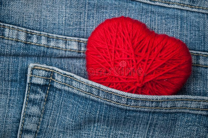 red woolen shaped heart in blue jeans pocket stock images
