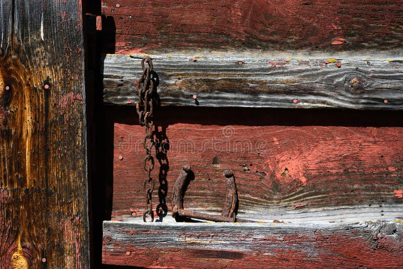 Detail of farm shed with rusty chain. Red worn paint on wood panels of an old farm shed and rusty chain hanging on a nail stock image