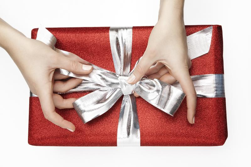 Red, wrapped gift with a silver ribbon fixed by female hands on a white background royalty free stock image