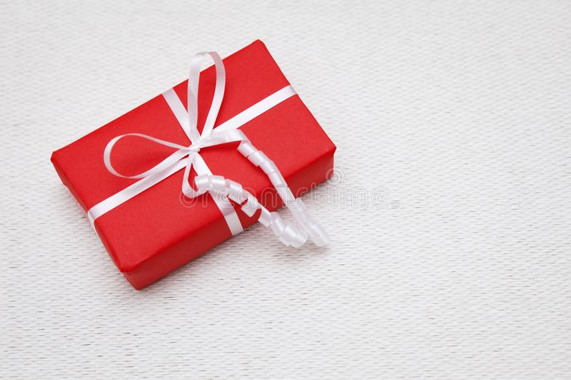 Red wrapped gift with a white ribbon on a woven, textured ecru backround. royalty free stock image