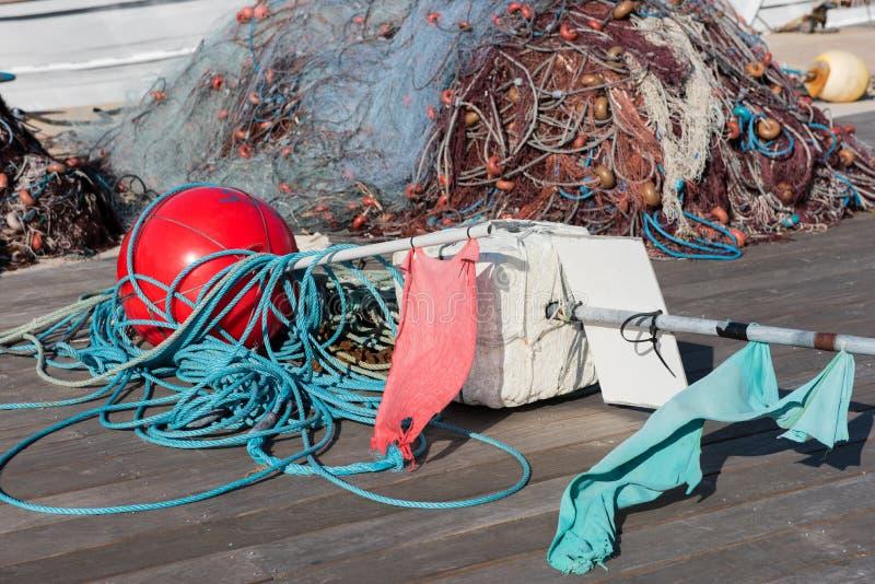Red y boyas de pesca en el puerto en el sol fotografía de archivo