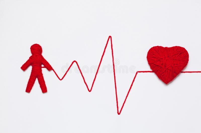 Yarn heart and human figure with thread like ECG pattern. Red yarn heart and human figure with thread like ECG pattern, isolated on white background stock images