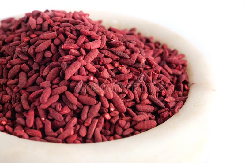Red yeast fermented rice. On mortar grinding bowl stock image