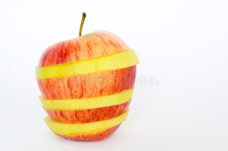Red and yellow apple. Red an yellow sliced apple over white background stock image