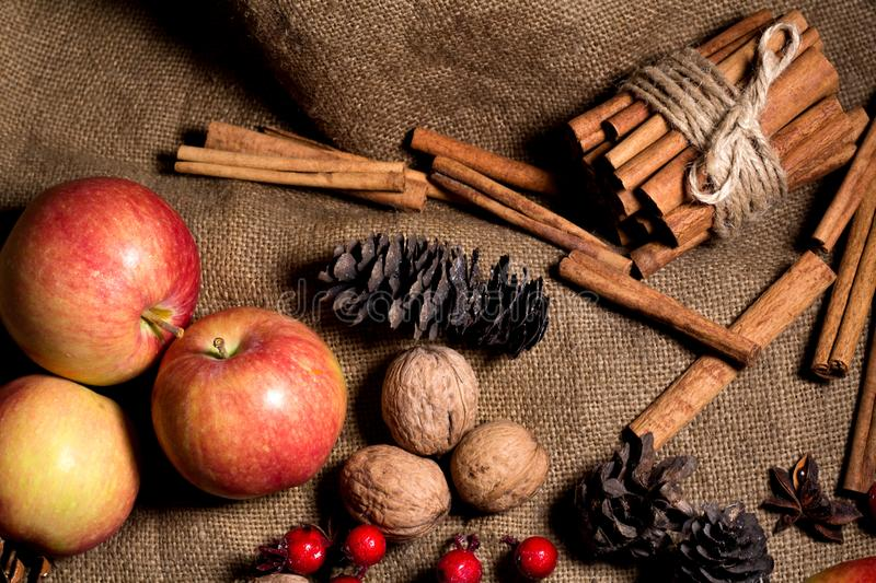 Red and yellow apples, cinnamon on a sackcloth background. stock photo