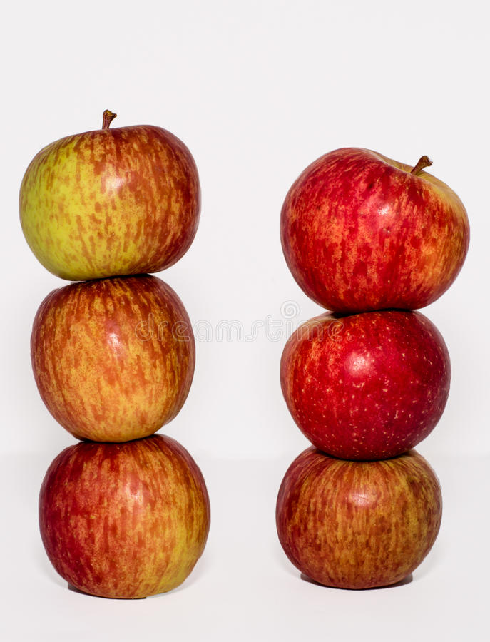 Red and yellow apples stacked on white royalty free stock image