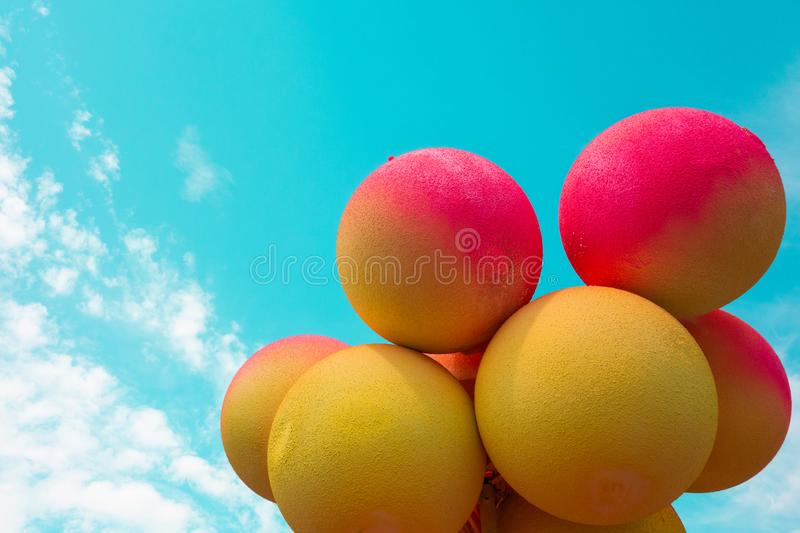 Red and yellow balls balloons on cloud sky background. Vivid holiday poster with copy space. Sunny happy day concept stock image
